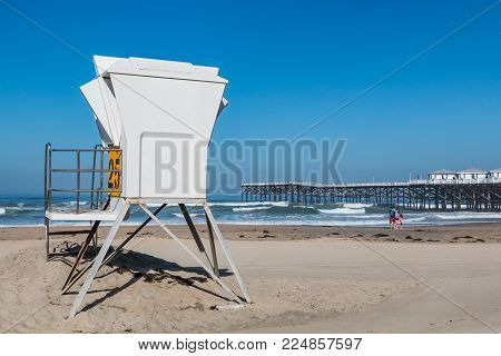 San Diego, California - April 21, 2017:  People Enjoy Pacific Beach Between A Lifeguard Tower And Cr