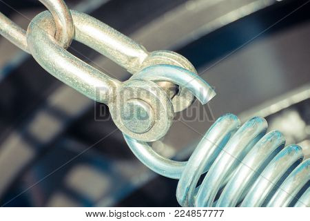 Closeup of steel spring on industrial or agricultural machine, detail and part of hydraulic or pneumatic machinery, engineering and technology concept