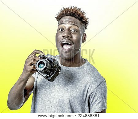young attractive and cool happy black afro American man holding digital reflex photo camera smiling excited isolated on yellow background in photographer learning and practicing photography hobby poster