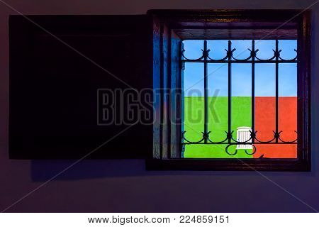A typical Cuban window with a lattice and a view of the red-green wall with a white window and a blue sky