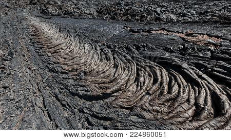 Lava field volcano landscape of Kamchatka Peninsula: view of smooth, undulating surface of black frozen lava flow, which wrinkled in tapestry-like folds and rolls resembling twisted. Active Plosky (Flat) Tolbachik Volcano in Russian Far East.