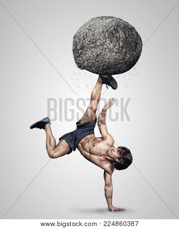 Shirtless sporty male upside down with grey stone on his leg.