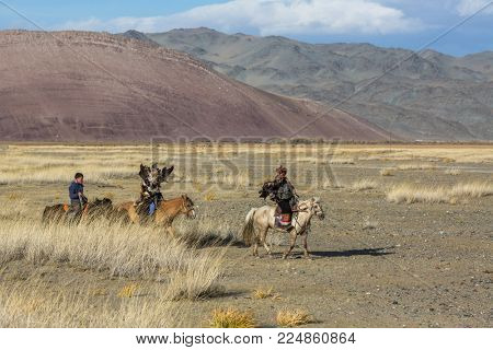 SAGSAY, MONGOLIA - SEP 28, 2017: Eagle Hunter teaches her young daughter hunting with birds of prey to the hare in desert mountain of Western Mongolia.