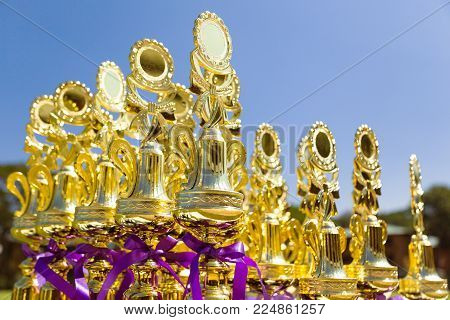 Shinny golden sport trophies lining up on an outdoor table against deep clear blue sky, ready to be handing out to the winners at a sport competition