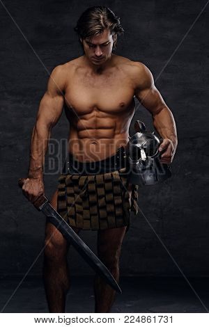 Portrait of shirtless muscular male in a Rome soldier costume holds silver gladiator helmet and an iron sword in a contrast dramatic studio light.