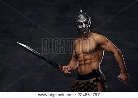 Brutal shirtless muscular male in a silver gladiator helmet holds an iron sword on grey background in a studio.