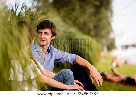 Love couple gazing at each other while sitting in park