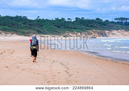 Pilgrim with backpack going on beach on the North way Camino de Santiago, Spain