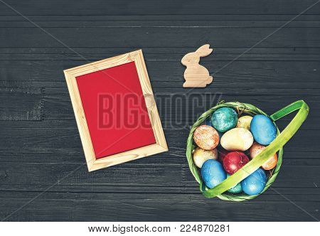 Easter 2018. Basket with Easter multicolored eggs, rabbit and blank frame for writing on a black background. Easter background or card. Close up, top view
