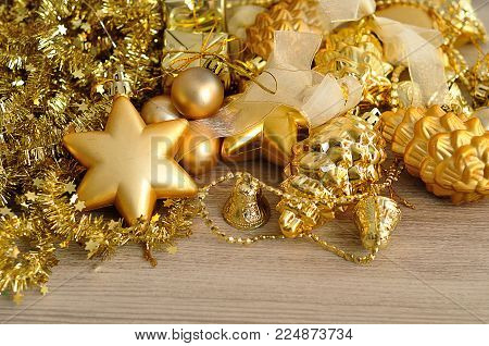 A variety of golden christmas tree decorations displayed with golden tinsel