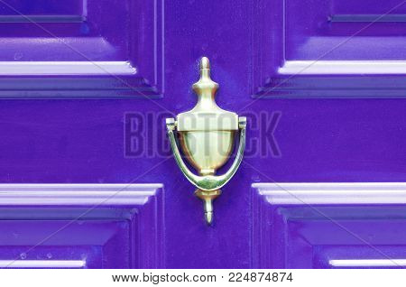 Old antique golden brass knocker on the abstract purple wooden doors for knocking close up