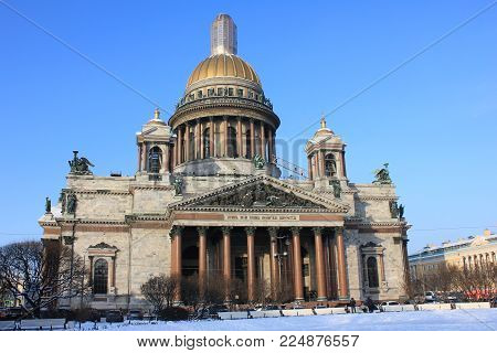 Saint Isaac's Cathedral and Museum Building in St. Petersburg, Russia. Russian Classical Old Religious Symbol Architecture on Sunny Cold Winter Snowy Day against Blue Sky Background Copy Space.