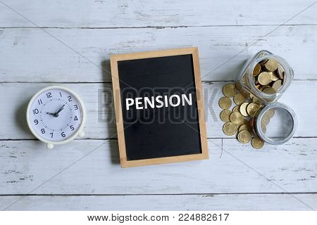 Top view of blackboard written with 'PENSION' with table clock and coins on white wooden background.
