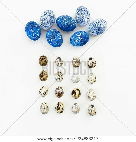Blue Speckled Easter Egg with quail eggs on white background. Flat lay. Top view. Cloud and rain made of easter eggs, creative concept