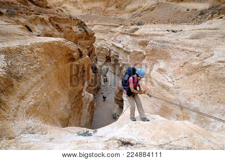 Female climber abseiling down from rock cliff in dry wadi in Judea desert.