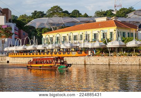 CLARKE QUAY, SINGAPORE - AUGUST 17, 2009: A traditional bumboat laden with tourists motors past Clarke Quay on the Singapore River.