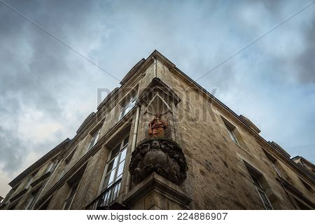 Medieval statue of Saint Jean in a niche on an  building of the old town of Bordeaux, France. Saint Jean is one of the patrons of Bordeaux, the biggest city in Southwestern France