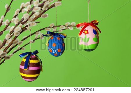 Three colored easter eggs on willow bouquet with pussy willows. Religious decoration. Paschal eggs on branches with furry catkins in vase. Salix. Front view, horizontal, on green background. Photo.