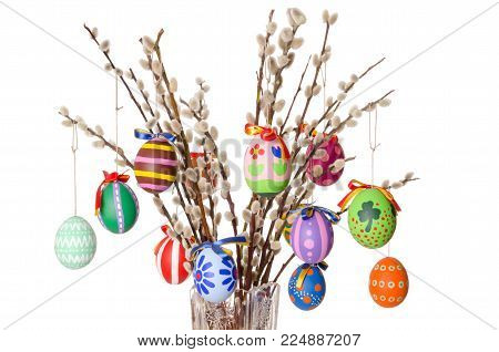 Colored easter eggs on willow bouquet with pussy willows. Religious decoration. Paschal eggs on branches with furry catkins in crystal vase. Salix. Front view, horizontal, on white background. Photo