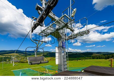 Empty chairlift in ski resort. Shot in summer with green grass and blue sky background
