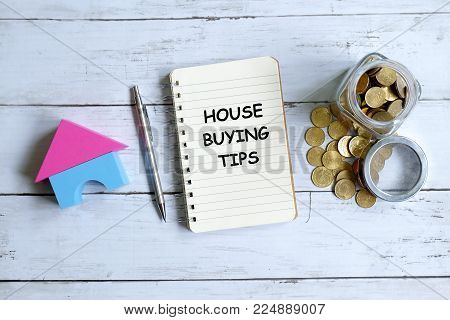 Top view of notebook written with 'HOUSE BUYING TIPS' with pen,house model and coins on white wooden background.