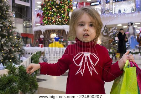 portrait of a pretty little girl in a red sweater with gifts at the beautifully decorated christmas trees with lights in the shopping mall. child was lost in the mall