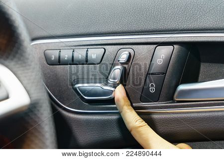 Hand Pressing The Button For For Adjusting The Chair Position In A Luxury Car.