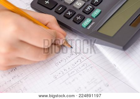 Calculator In The Action Hands During Mathematical Lesson. School Concept.