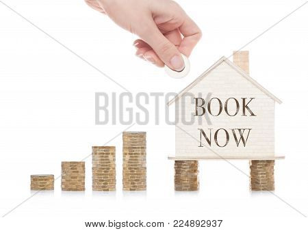 Wooden house model standing on coins and hand holding the coin with conceptual text. Book Now