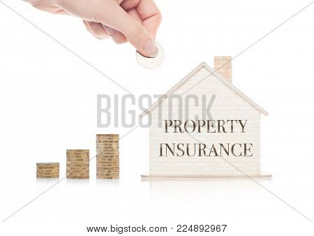 Wooden house model with coins next to it and hand holding the coin with conceptual text. Property Insurance