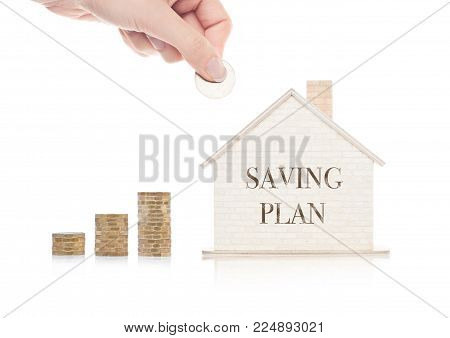 Wooden house model with coins next to it and hand holding the coin with conceptual text. Saving Plan