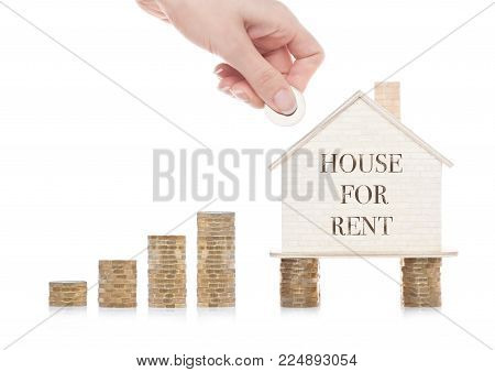 Wooden house model standing on coins and hand holding the coin with conceptual text. House for rent