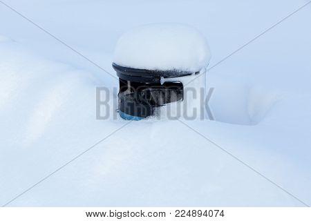 A trashbin sorrounded by deep deep white snow