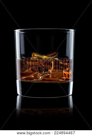 Elegant glass of whiskey with ice cubes on black background with reflection