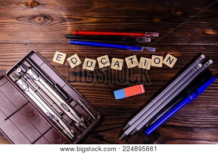 Case of drawing instruments, pencils and eraser on rustic wooden table. Education inscription. Top view