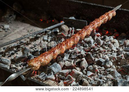Appetizing lula kebab grilled on metal skewer. Cooking meat.