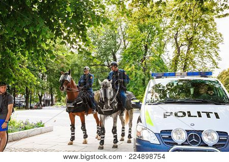 Oslo, Norway-August 13, 2014 -The  mounted police at the Norwegian parliament building and demonstration during a protest, Stortinget.