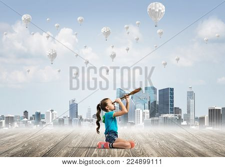 Cute kid girl sitting on wooden floor and aerostats flying in air