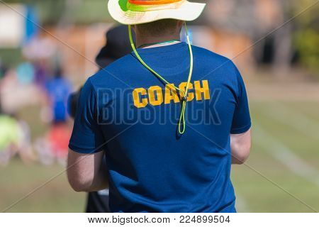 back of a coach's blue color shirt with the word Coach in yellow color written on, blurred outdoor sport field background