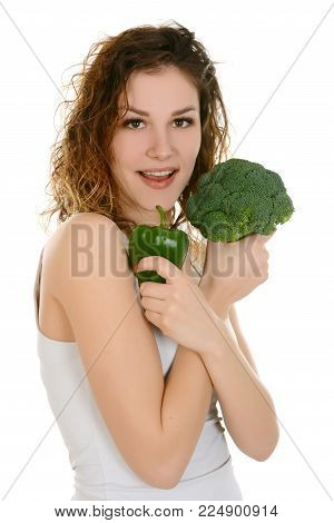 Young smiling woman holding broccoli and green peper, isolated on white background