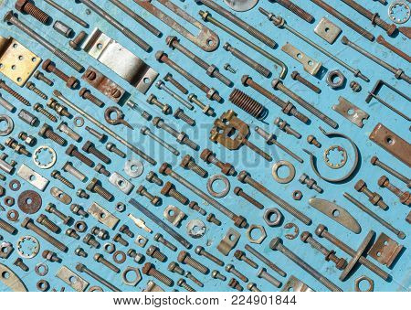 set of old rusty metal screws, nuts and bolts on a blue background. Flat lay, top view