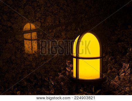 Garden Light With Cross On It Reflecting Against A Marble Tile Wall. An Outdoor Yellow And Orange Gl