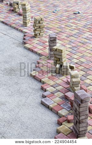 Paving slabs by mosaic close up. Road paving, construction . Fixed tessellated sidewalk tile. Colored concrete paving slab
