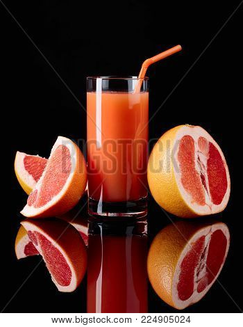 Glass Of  Grapefruit Juice And Cut Fruits On Black Background.
