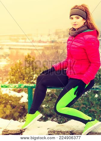 Outdoor sport exercising, sporty outfit ideas. Woman wearing warm sportswear relaxing after exercising outside during winter.