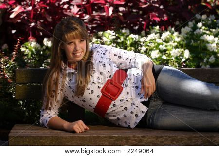 Pretty Teenage Girl Laying On A Park Bench