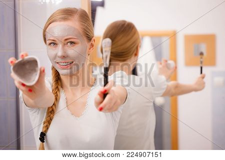 Skin care. Young woman holding in hands brush and clay mud mask to apply on skin face, in bathroom. Girl taking care of her oily compexion. Spa wellbeing.