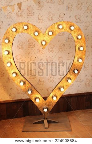Heart is decorated with lights for Valentine's Day on light background