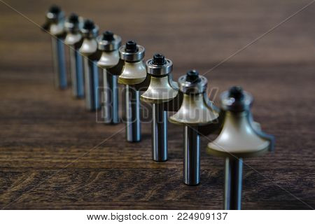 Mills exposed in a row on a wooden dark background. Milling cutter and router bit. Corner round bit for wood and plastic. Carbide drill or milling cutter.
