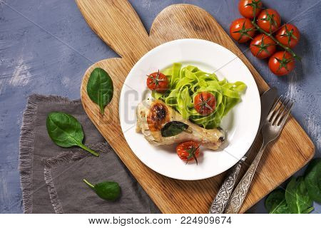 Baked chicken with pasta. Green paste with spinach. Top on top, copy space